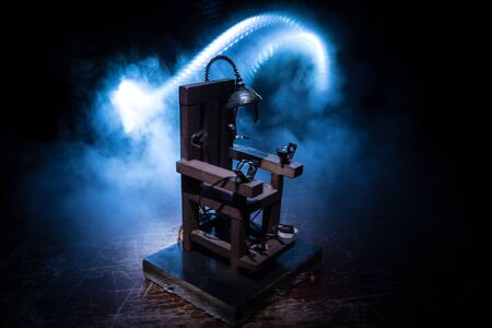 Death penalty electric chair miniature on dark. Creative artwork decoration. Image of an electric chair scale model on a dark backgorund Foto de archivo