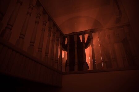 Inside of old creepy abandoned mansion. Silhouette of horror ghost standing on castle stairs to the basement. Horror Halloween concept Standard-Bild