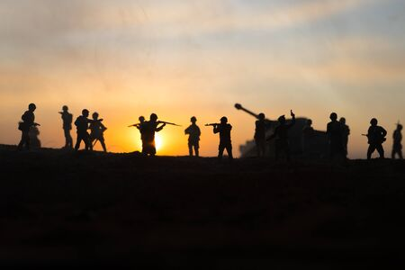 War Concept. Military silhouettes fighting scene on war fog sky background, World War Soldiers Silhouette Below Cloudy Skyline sunset. Selective focus Stock Photo