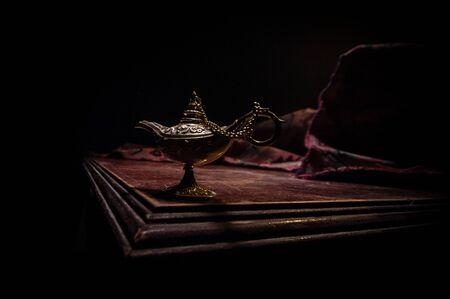 Antike Aladdin arabische Nächte Genie-Stil Öllampe mit weichem Licht, weißem Rauch, dunklem Hintergrund. Konzept der Wunschlampe
