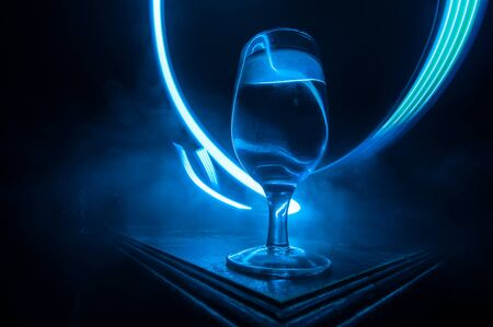 Goblet of wine on wooden table with beautiful toned lights on background. Glasses of wine on dark background. Selective focus. Club drink concept
