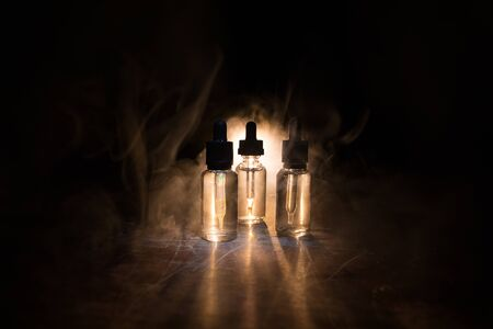 Vape concept. Smoke clouds and vape liquid bottles on dark background. Light effects. Useful as background or vape advertisement or vape background. Selective focus Imagens