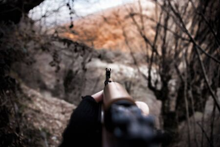 Shooter aiming target with assault rifle weapon. Dangerous bandit aiming gun. Special soldier during the military operation mountain road. Selective focus