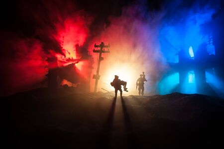 Silhouette of a man carrying injured girl from fire. Rescue savior concept. Military officer running out with woman from burned out city destroyed in war. Creative artwork decoration. Selective focus