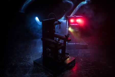 Death penalty electric chair miniature on dark. Creative artwork decoration. Image of an electric chair scale model on a dark backgorund Standard-Bild - 143959265