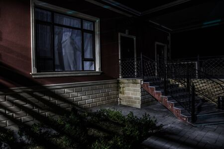 Old house with a Ghost in the at night. Horror silhouette at the window. Surreal lights. Horror Halloween concept Standard-Bild - 143959280