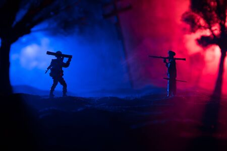 Military soldiers silhouettes with bazooka and rpg. War Concept. Military silhouettes fighting scene on war fog sky background, Mojahed with rpg and us soldier with bazooka at sunset. Attack scene Stock Photo