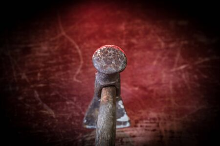 Old vintage hammer on a wooden table in front of a dark toned misty background. Selective focus.