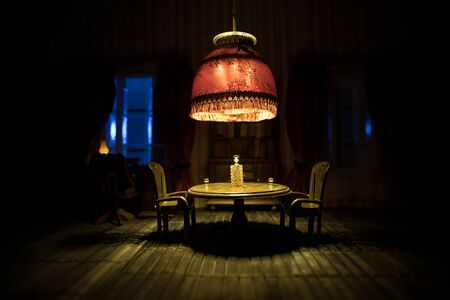 A realistic dollhouse living room with furniture and window at night. Artwork table decoration with handmade realistic dollhouse. Selective focus. Banque d'images