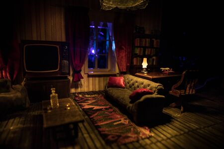A realistic dollhouse living room with furniture and window at night. Artwork table decoration with handmade realistic dollhouse. Old retro style Television. Selective focus. Stock Photo