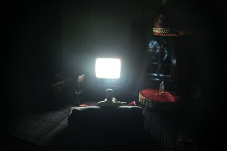 A realistic dollhouse living room with furniture and window at night. Artwork table decoration with handmade realistic dollhouse. Silhouette of a man watching TV in a dark room. Selective focus