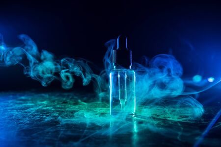Vape concept. Smoke clouds and vape liquid bottles on dark background. Light effects. Useful as background or vape advertisement or vape background. Selective focus