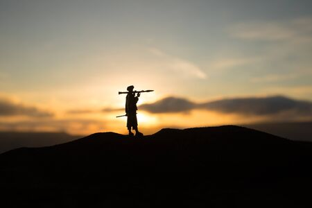 Military soldiers silhouettes with bazooka and rpg. War Concept. Military silhouettes fighting scene on war fog sky background, Mojahed with rpg at sunset. Stock Photo