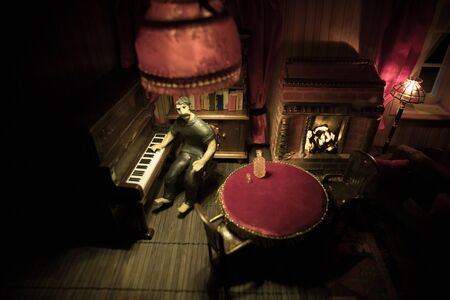 A realistic dollhouse living room with furniture and window at night. Man sitting at the old piano in dark room. Selective focus.