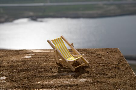Miniature doll lounger on sand at balcony with view on mountains and lake. Corona virus stay home concept. Funny decoration. Stay at home to reduce risk of infection. Selective focus. Stock Photo