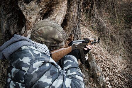 Man in mask with assault rifle ready to attack in the forest. Dangerous bandit aiming gun. Special soldier during the military operation on mountain road. Selective focus