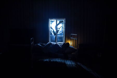 Man comfortably sleeping in his bed at night. A realistic dollhouse bedroom with furniture and window at night. Selective focus