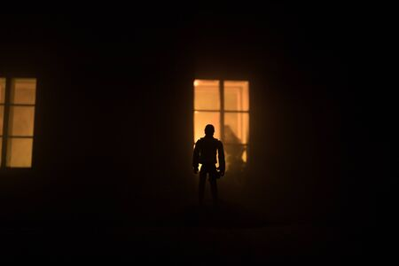 Silhouette of a man standing near window of dollhouse at night. Love concept. Selective focus Archivio Fotografico