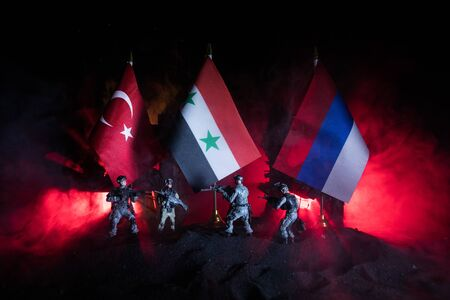 Closeup, flags of Russia, Syria and Turkey against destroyed city at night. Decorated diorama. Concept of crisis of war and political conflicts between nations. Selective focus 免版税图像