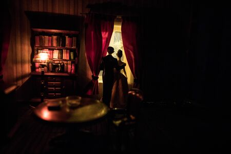 A realistic dollhouse living room with furniture and window at night. Romantic couple sitting on window. Artwork table decoration with handmade realistic dollhouse. Selective focus. Standard-Bild