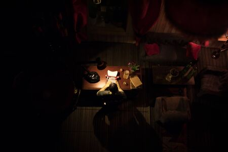 A realistic dollhouse living room with furniture and window at night. Man sitting on table in dark room. Selective focus. Stock Photo