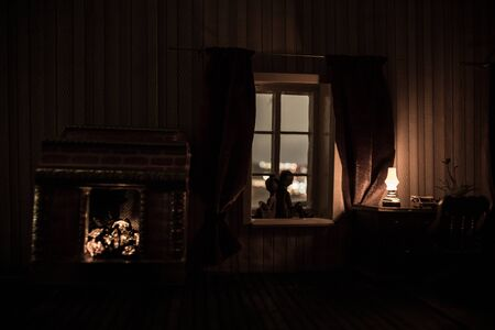 A realistic dollhouse living room with furniture and window at night. Romantic couple sitting on window. Artwork table decoration with handmade realistic dollhouse. Selective focus. Stock Photo