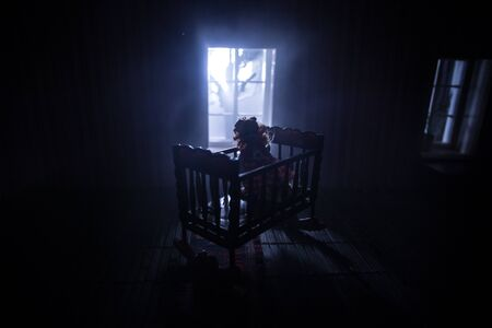Old creepy eerie baby crib near window in dark room. Scary baby silhouette in dark. A realistic dollhouse living room with furniture and window at night. Selective focus