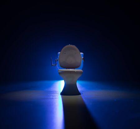 Creative concept. Miniature white toilet bowl on dark foggy background. Selective focus