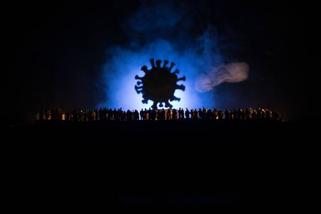 Coronavirus 2019-nCov novel coronavirus concept. Crowd looking on big Corona virus model at night with fog and backlight. Creative artwork decoration. Selective focus.