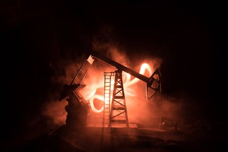 Oil pump and oil refining factory at night with fog and backlight. Energy industrial concept. Selective focus. Artwork decoration. Banque d'images
