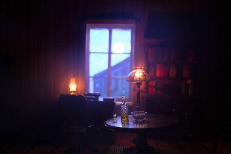 A realistic dollhouse living room with furniture and window at night. Artwork table decoration with handmade realistic dollhouse. Selective focus. Foto de archivo