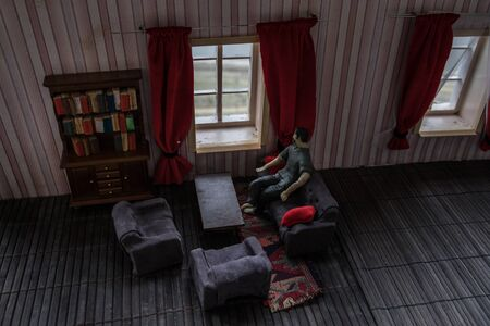 Sad, depressed man during the coronavirus quarantine staying at home, going mental and crazy. Covid-19 home isolation concept. Realistic dollhouse artwork decoration . Selective focus Stock Photo
