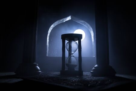 Time concept. A realistic Arabian interior miniature with window and columns. Silhouette of hourglass inside room. Abstract surreal idea with empty space. Selective focus