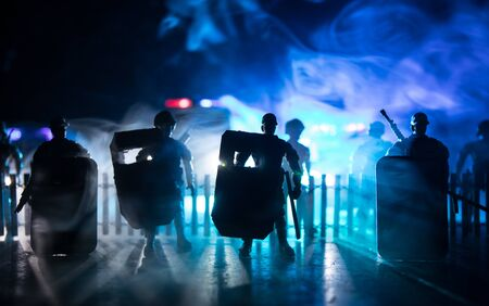 Corona virus concept with police. Stay home for precautionary measures to prevent from corona virus. Anti-riot police give signal to be ready. Smoke on a dark background with lights. Selective focus Stok Fotoğraf