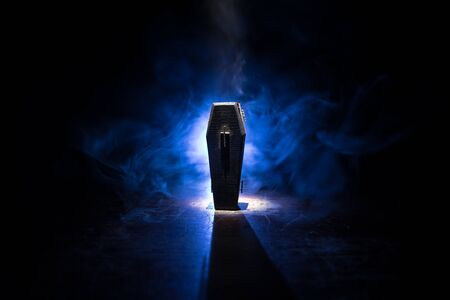 Creative artwork. Miniature wooden coffin on a table with dark background. Selective focus Standard-Bild