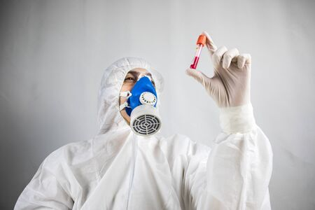Coronavirus covid 19 infected blood vial in hand of female doctor with surgical mask and glows. Coronavirus covid 19 reseach laboratory, coronavirus covid-19 vaccine research. Selective focus Foto de archivo