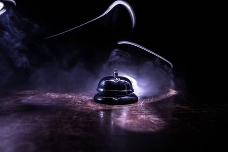 Calling service bell on wooden table with toned lights on dark background. Hotel reception bell, service bell on the table, selective focus