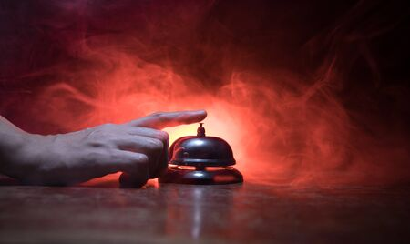 Calling service bell on wooden table with toned lights on dark background. Hotel reception bell, Hand ringing in service bell , selective focus