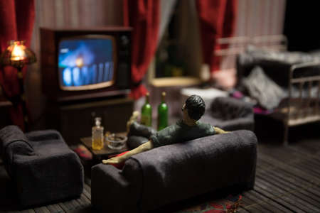 A realistic dollhouse living room with furniture and window at night. Artwork table decoration with handmade realistic dollhouse. Man wathing retro style Television in dark room. Selective focus. Standard-Bild