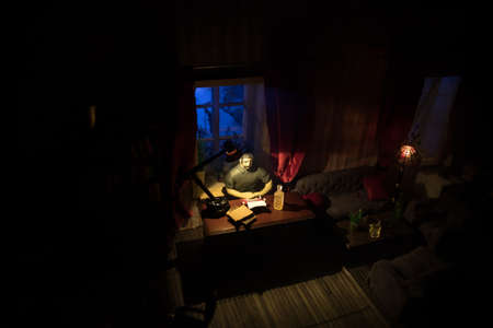 A realistic dollhouse living room with furniture and window at night. Man sitting on table in dark room. Selective focus. Stock Photo - 152012176