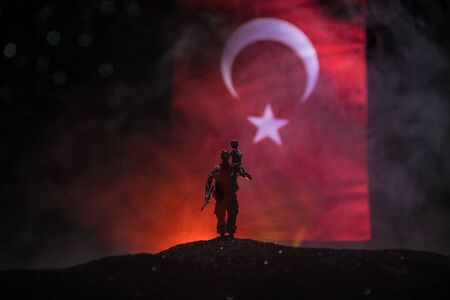Turkish army concept. Silhouette of soldiers against a Turkish flag. Creative artwork decoration. Turkish soldier carrying little boy on his shoulder. Selective focus