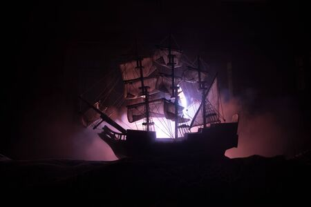 Black silhouette of the pirate ship in night. night scene of ghost pirate ship in the sea with mysterious light. Selective focus