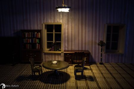 A realistic dollhouse living room with furniture and window at night. Artwork table decoration with handmade realistic dollhouse. Selective focus. Stock Photo