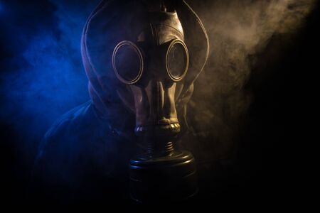 Environmental disaster. Post-apocalyptic survivor in gas mask on a dark background. Dramatic portrait of a man wearing a gas mask. Means for radiation protection. Selective focus