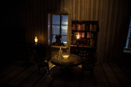 A realistic dollhouse living room with furniture and window at night. Romantic couple sitting on window. Artwork table decoration with handmade realistic dollhouse. Selective focus. Banco de Imagens