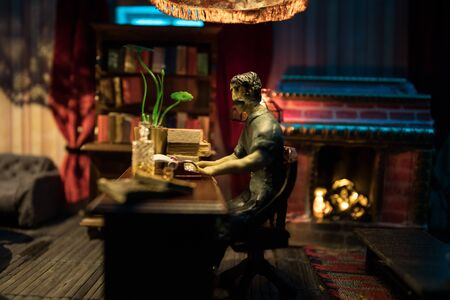 A realistic dollhouse living room with furniture and window at night. Man sitting on table in dark room. Selective focus. Banco de Imagens