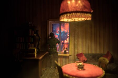A realistic dollhouse living room with furniture and window at night. Stay home stay safe coronavirus concept. Selective focus.