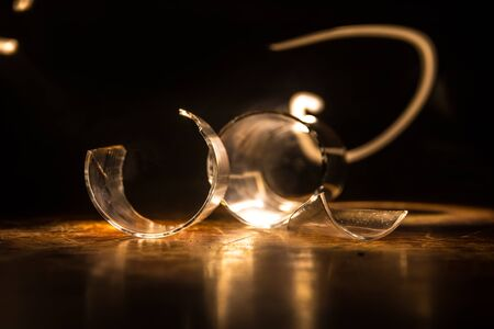 Drink, broken glass concept. Broken glasses on wooden table at dark toned background with fog. Selective focus Stock Photo - 150115079