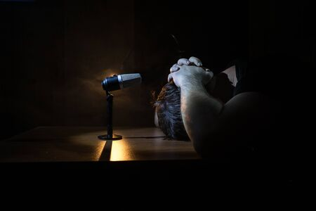 Caucasian man news broadcaster sat at a desk with microphone in dark room. Performer with microphone. Male musician singing into a microphone. Shot on a black background. Dark atmosphere Standard-Bild
