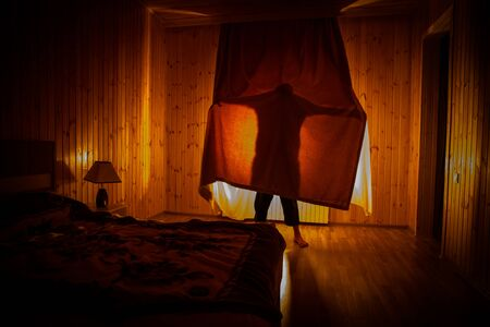 Horror silhouette in window with curtain inside bedroom at night. Horror scene. Halloween concept. Blurred silhouette of ghost Standard-Bild
